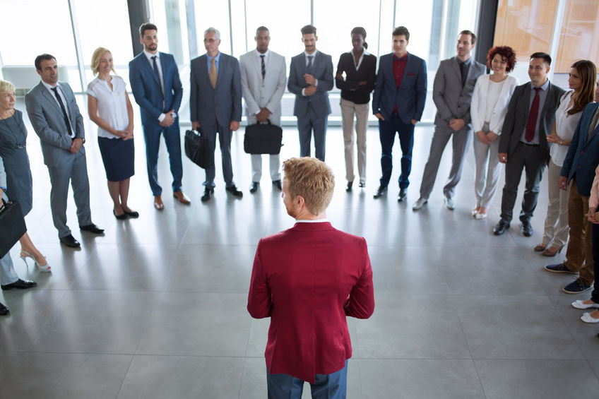 64816649 - young leader standing in front of his successful business team