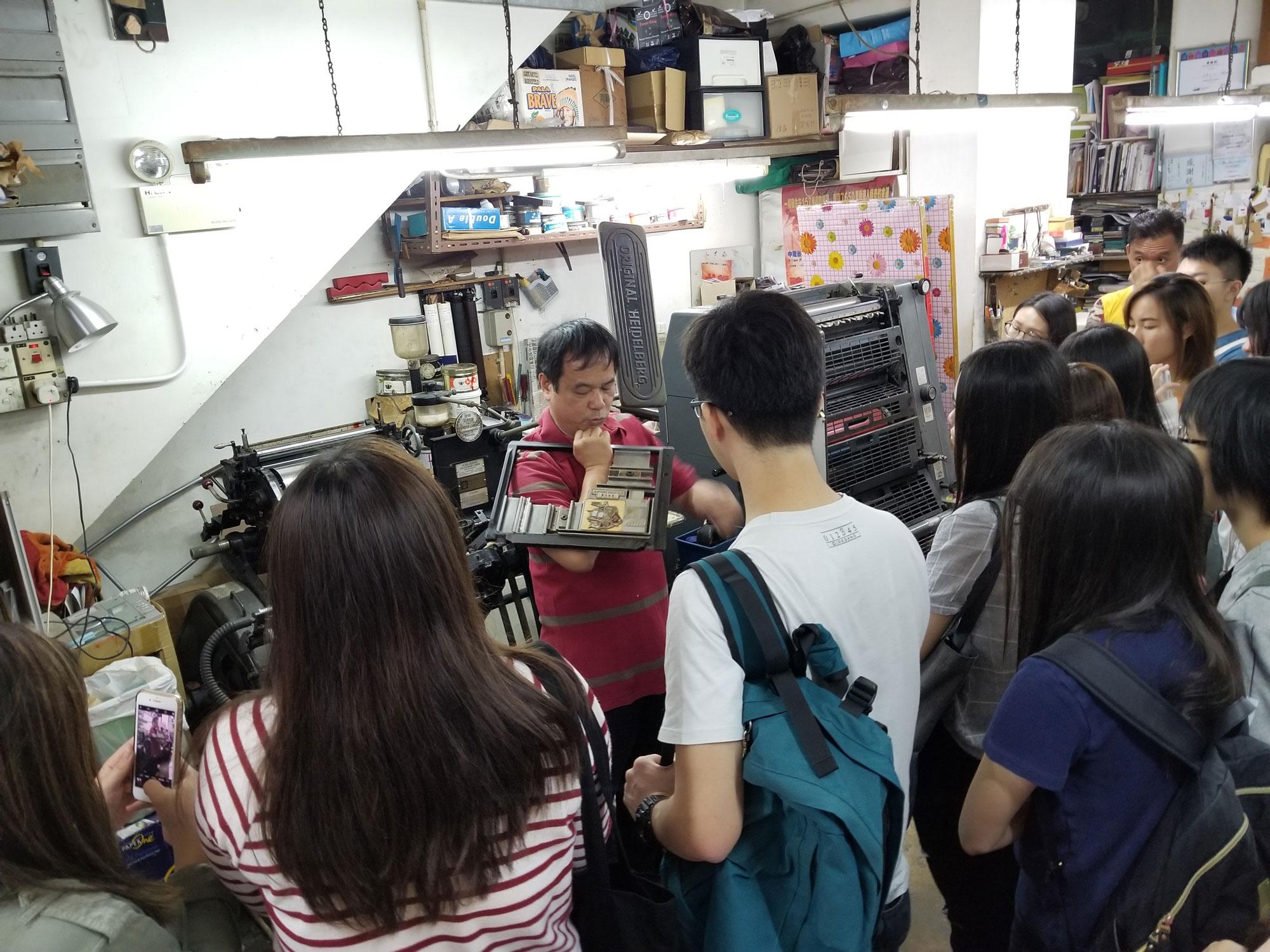 老闆介紹舊式活字印刷機的操作